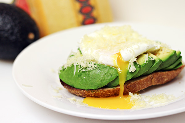 Sliced Avocados on Sourdough Toast with Poached Egg and shredded Jarlsberg Cheese