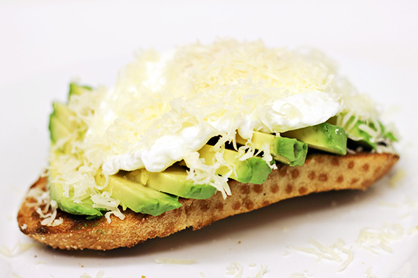 Avocado Slices on Sourdough Toast with Poached Egg and Shredded Jarlsberg Cheese