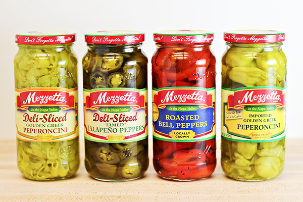 Four jars of Mezzetta brand products, including Deli-Sliced Golden Greek Peperoncini, Deli-Sliced Tamed Jalapeno Peppers, Roasted Red Peppers, and Imported Golden Greek Peperoncini