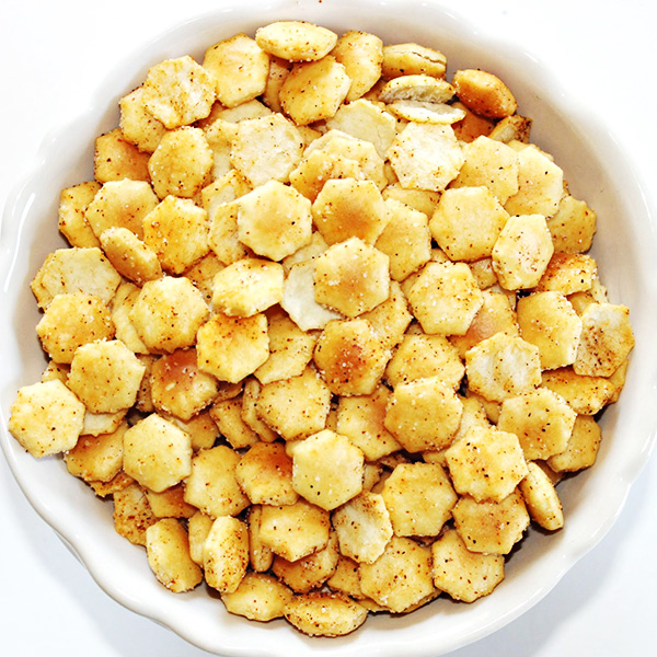 Overhead photo of oyster crackers seasoned with Tony Chachere's Original Creole Seasoning, served in a while bowl