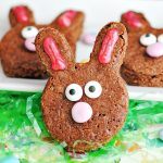 Three chocolate brownie Easter bunnies on white plate with Easter grass