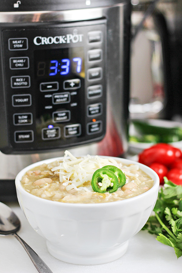 Bowl of White Chicken Chili topped with shredded cheese and sliced jalapenos with the Crock-Pot Express Crock Multi-Cooker in background