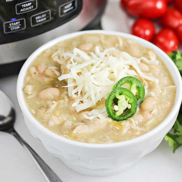 Closeup of bowl of Easy Pressure Cooker White Chicken Chili, topped with shredded cheese and sliced jalapenos for garnish, and grape tomatoes in the background.