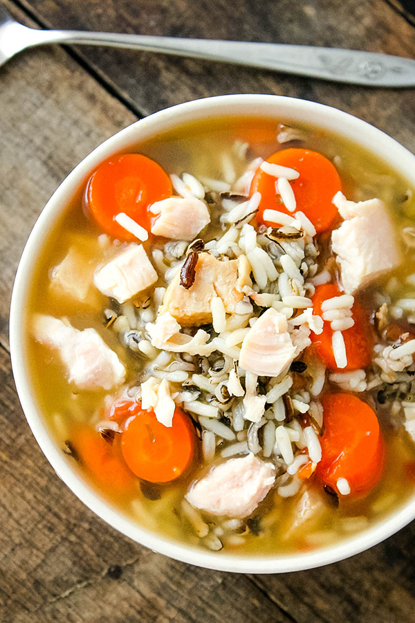 Bowl of homemade soup with chicken, wild rice, and carrots.
