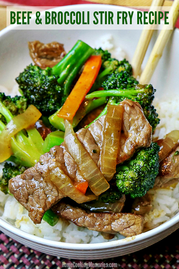 Easy Beef and Broccoli Stir Fry Recipe shown prepared with carrots and onions. Served over white rice in a white bowl with wooden chopsticks.