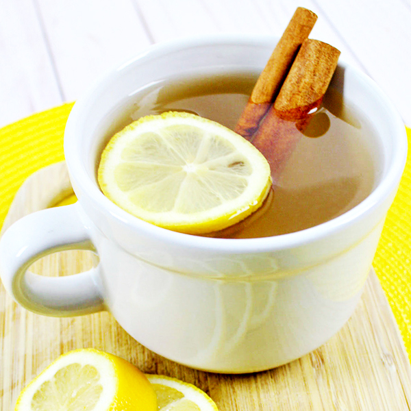 Hot Toddy drink in a white mug with a lemon slice and cinnamon sticks