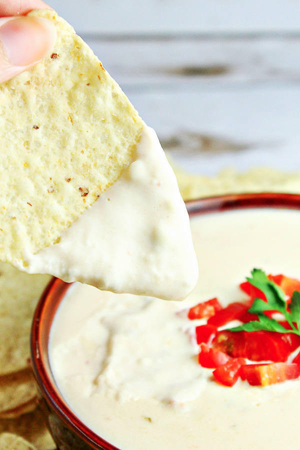 Tortilla chip being dipped into Homemade White Queso Dip in a brown bowl, and topped with diced tomatoes