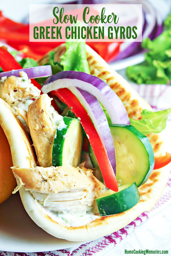 Slow Cooker Greek Chicken Gyros Recipe in folded pita bread with sliced cucumbers, tomatoes, red bell pepper slices, lettuce, and tzatziki sauce on a white plate