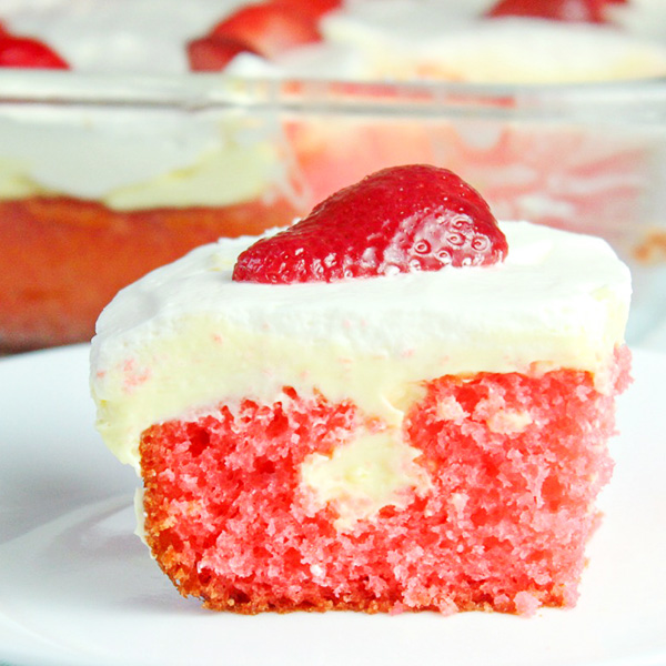 A piece of Lemon Strawberry Poke Cake on a white plate with the remaining cake in a 13x9 baking dish sitting behind