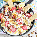 Banana Split Smores Dip Recipe served in a cast iron skillet with graham cracker dippers