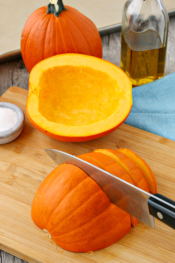 Cutting a fresh pumpkin into sliced wedges, before baking