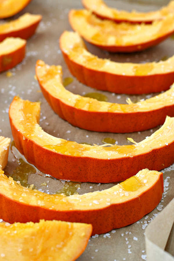 Pumpkin slices on a baking sheet, drizzled with olive oil and seasoned with salt for baking.