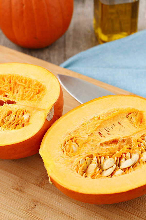 A fresh pumpkin cut in half, showing the seeds and fibers, before cooking