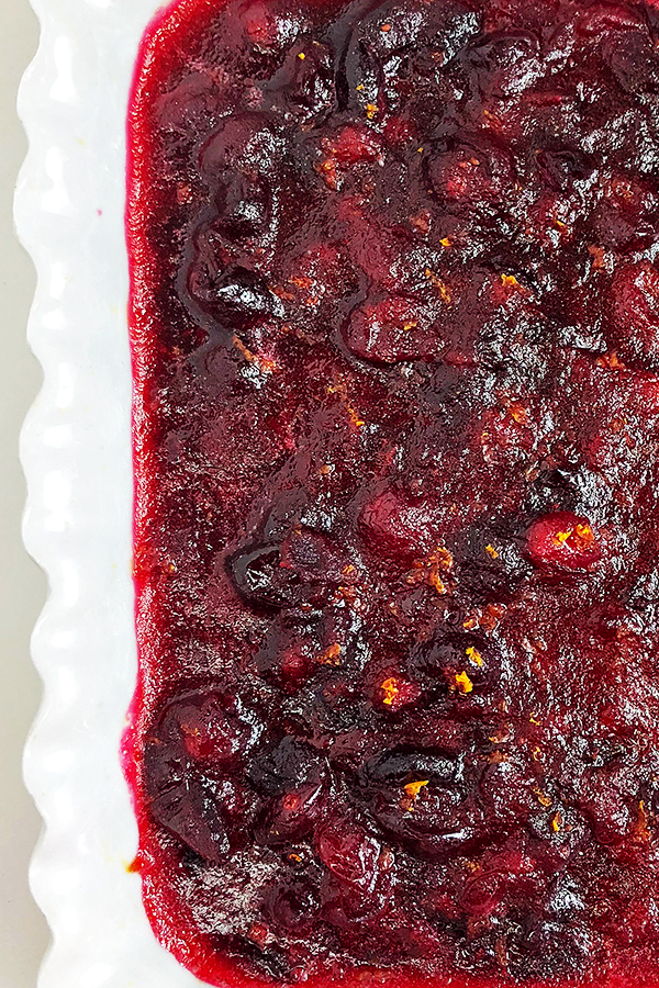 Homemade cranberry sauce with orange zest in a white dish
