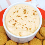 Bowl of pumpkin dip surrounded by gingersnap cookies.