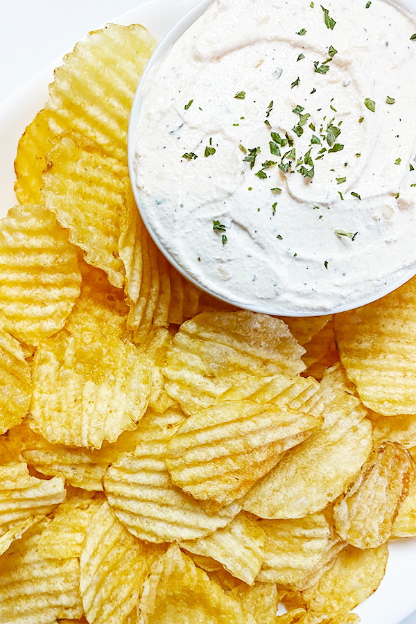 Bowl of Homemade Onion Chip Dip, surrounded by a plate of ripple potato chips on a white platter