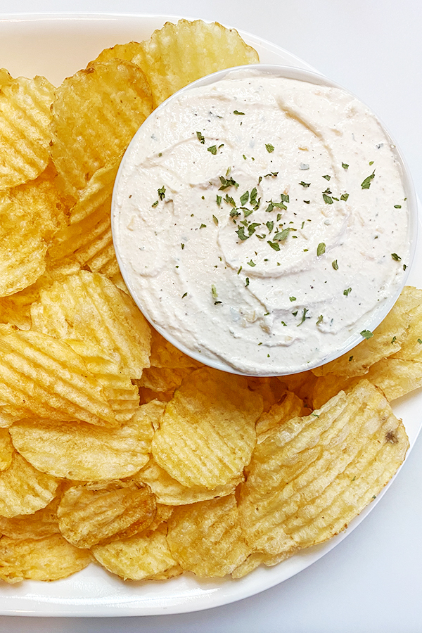 Plate of potato chips with a bowl of homemade onion dip